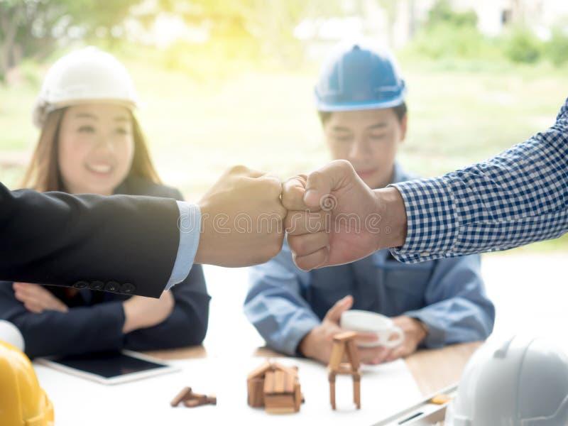Επιχείρηση, κτήριο, ομαδική εργασία, χειρονομία και έννοια ανθρώπων - ομάδα χαμογελώντας οικοδόμων hardhats που χαιρετούν το ένα  στοκ εικόνα
