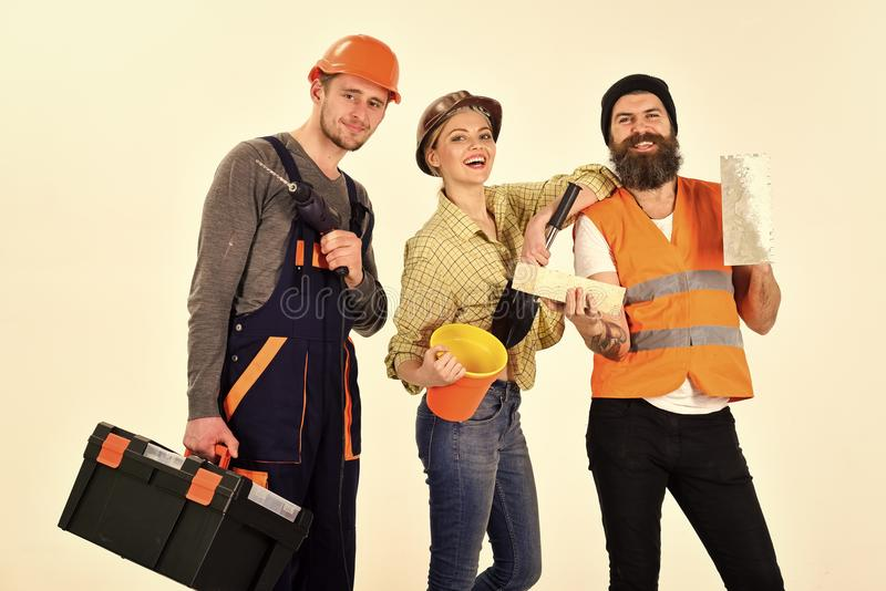 Επιχείρηση των εύθυμων εργαζομένων, οικοδόμος, επιδιορθωτής, γυψαδόρος Άνδρας και γυναίκα με τα πρόσωπα χαμόγελου στο κράνος και  στοκ φωτογραφία