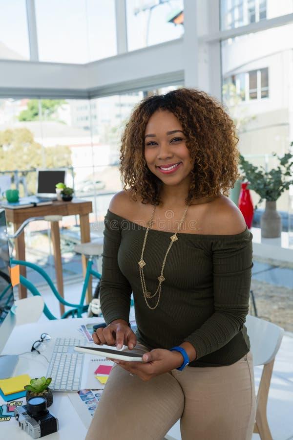 Επιχείρηση χαμόγελου που χρησιμοποιεί την ψηφιακή ταμπλέτα καθμένος στο γραφείο στην αρχή στοκ φωτογραφία με δικαίωμα ελεύθερης χρήσης