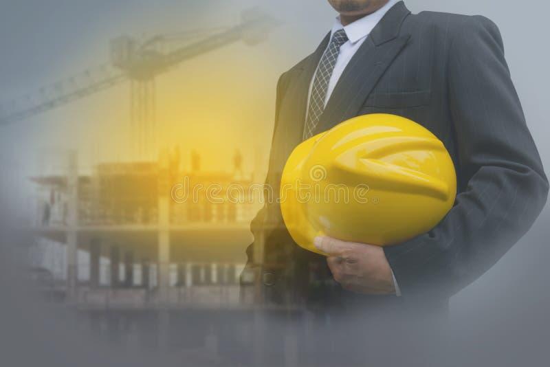 Επιχειρηματίας ή ανώτερος υπάλληλος ασφάλειας που κρατά το κίτρινο κράνος στοκ εικόνα με δικαίωμα ελεύθερης χρήσης