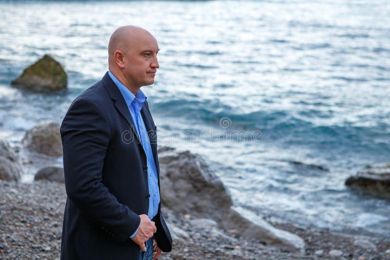 Επιχειρηματίας ατόμων σε ένα κοστούμι που στέκεται στην παραλία στοκ εικόνες με δικαίωμα ελεύθερης χρήσης
