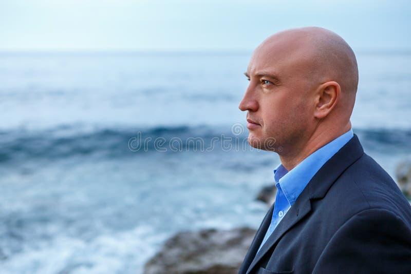 Επιχειρηματίας ατόμων σε ένα κοστούμι που στέκεται στην παραλία στοκ φωτογραφία
