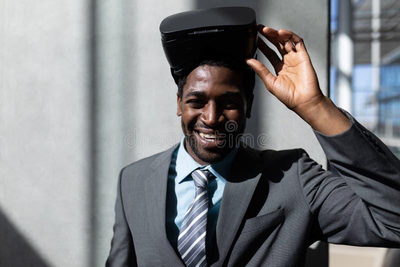 Επιχειρηματίας αφροαμερικάνων με την κάσκα εικονικής πραγματικότητας που εξετάζει τη κάμερα στην αρχή στοκ φωτογραφία με δικαίωμα ελεύθερης χρήσης