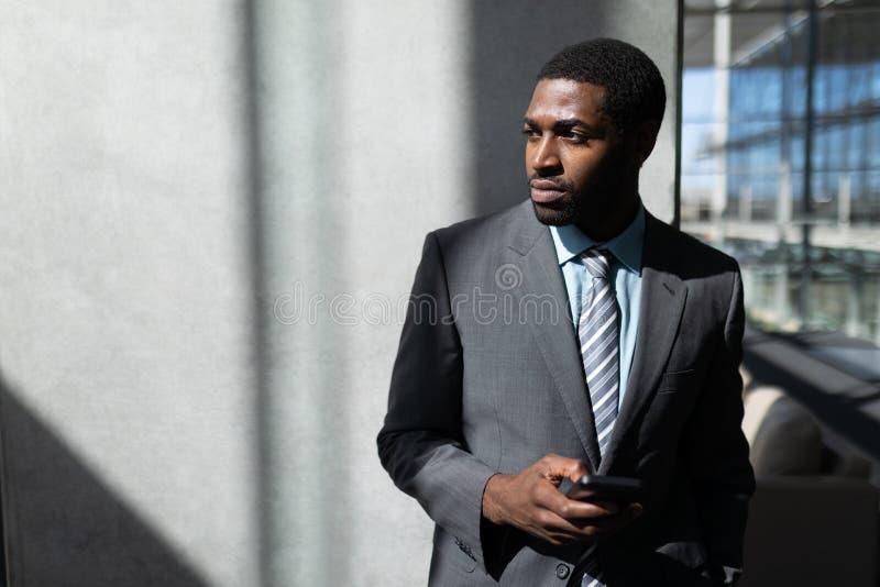 Επιχειρηματίας αφροαμερικάνων με το κινητό τηλέφωνο που φαίνεται μακριά στην αρχή στοκ εικόνες