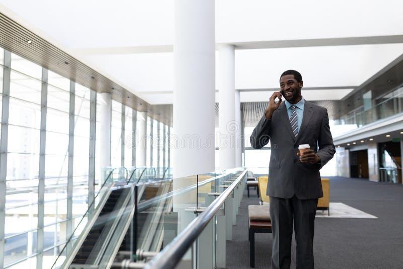 Επιχειρηματίας αφροαμερικάνων με το φλυτζάνι καφέ που μιλά στο κινητό τηλέφωνο στην αρχή στοκ φωτογραφίες