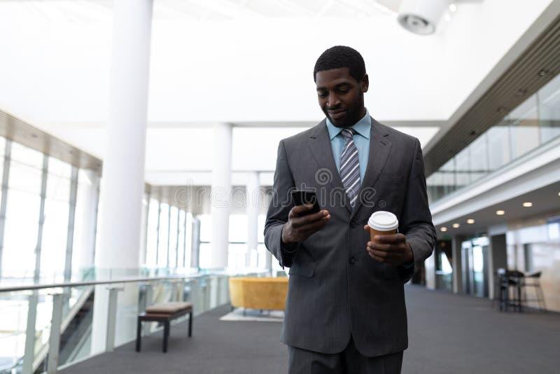 Επιχειρηματίας αφροαμερικάνων με το φλυτζάνι καφέ που χρησιμοποιεί το κινητό τηλέφωνο στην αρχή στοκ φωτογραφία