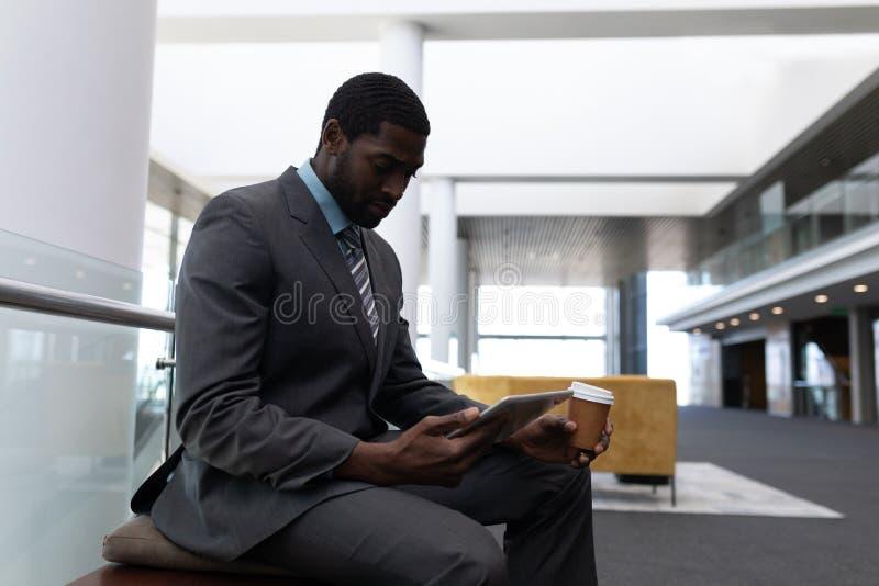 Επιχειρηματίας αφροαμερικάνων με το φλυτζάνι καφέ που χρησιμοποιεί την ψηφιακή ταμπλέτα στην αρχή στοκ φωτογραφίες