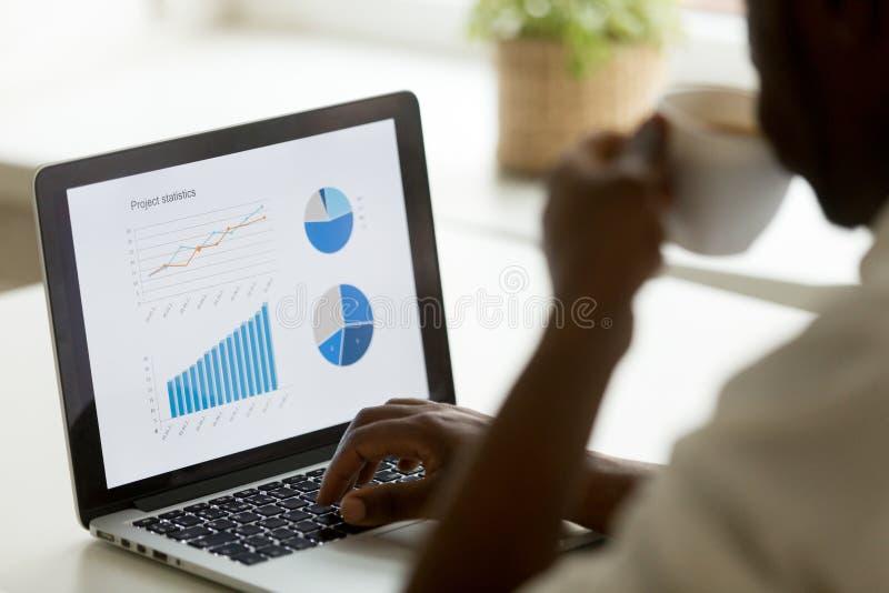 Επιχειρηματίας αφροαμερικάνων που εργάζεται με τις στατιστικές προγράμματος όσον αφορά στοκ εικόνες
