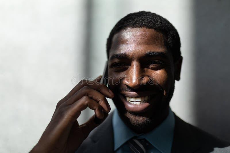 Επιχειρηματίας αφροαμερικάνων που μιλά στο κινητό τηλέφωνο στην αρχή στοκ εικόνες