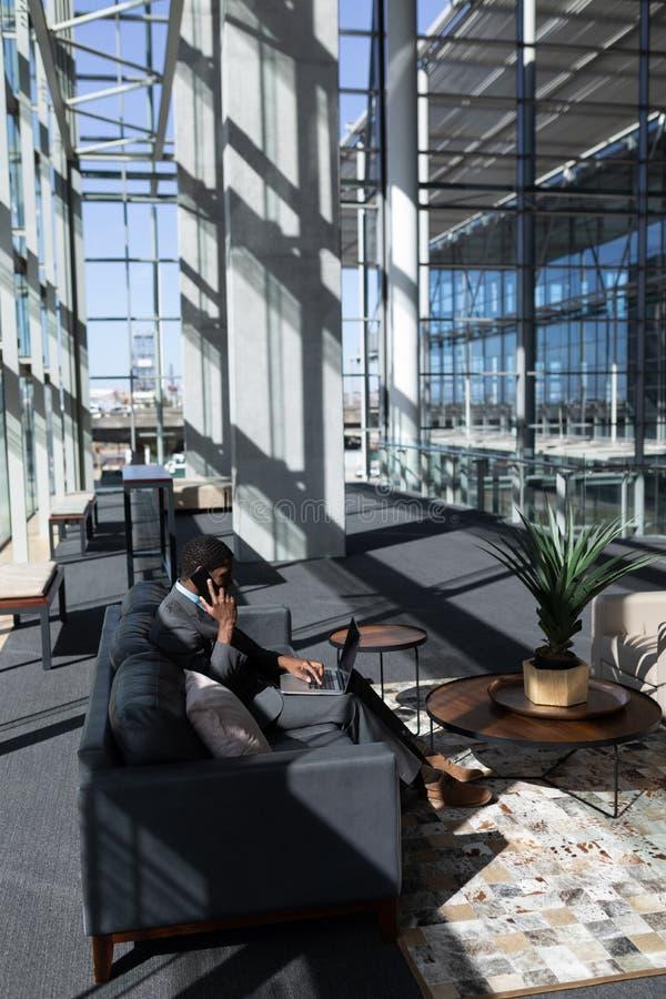 Επιχειρηματίας αφροαμερικάνων που μιλά στο κινητό τηλέφωνο χρησιμοποιώντας το lap-top στον καναπέ στο σύγχρονο γραφείο στοκ εικόνα με δικαίωμα ελεύθερης χρήσης