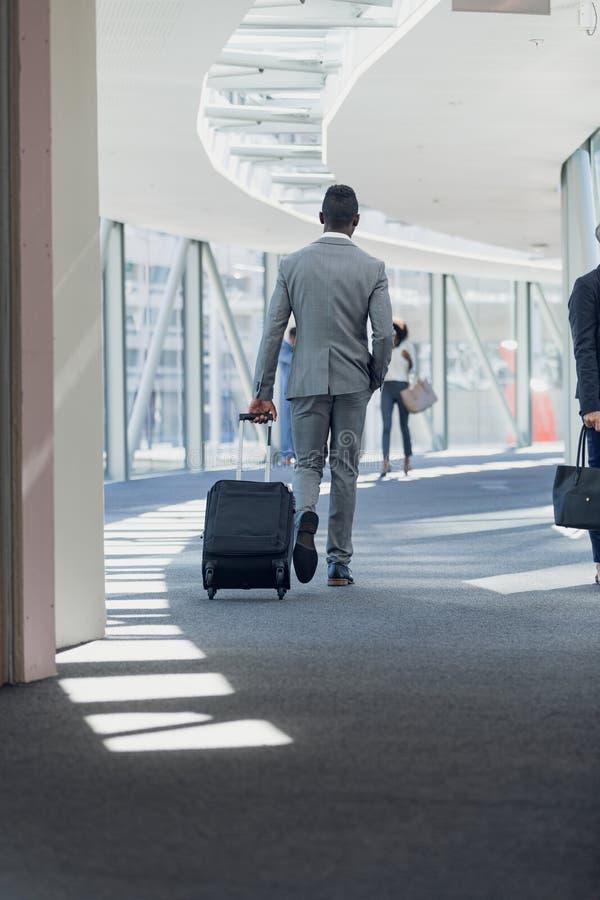 Επιχειρηματίας αφροαμερικάνων που περπατά στο διάδρομο με τη βαλίτσα στο σύγχρονο γραφείο στοκ φωτογραφία