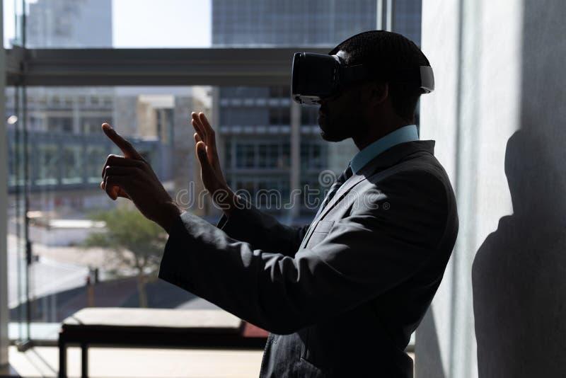 Επιχειρηματίας αφροαμερικάνων που χρησιμοποιεί την κάσκα εικονικής πραγματικότητας στην αρχή στοκ εικόνες