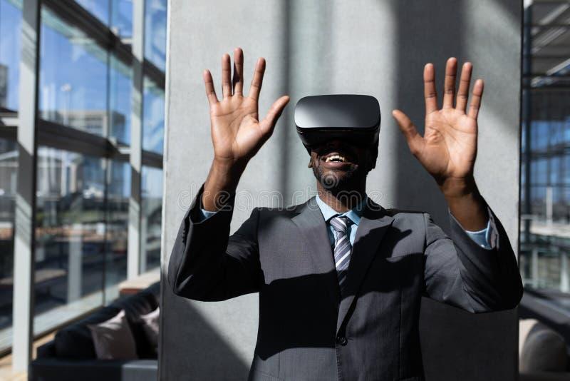 Επιχειρηματίας αφροαμερικάνων που χρησιμοποιεί την κάσκα εικονικής πραγματικότητας στην αρχή στοκ φωτογραφία με δικαίωμα ελεύθερης χρήσης
