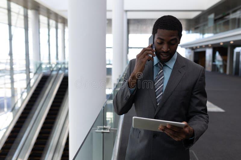 Επιχειρηματίας αφροαμερικάνων που χρησιμοποιεί την ψηφιακή ταμπλέτα μιλώντας στο κινητό τηλέφωνο στην αρχή στοκ εικόνα με δικαίωμα ελεύθερης χρήσης