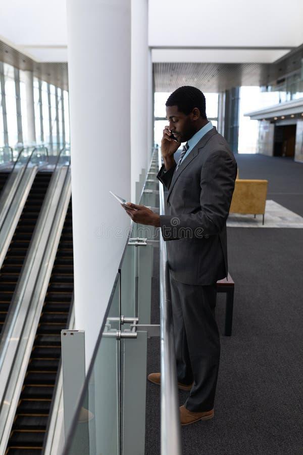 Επιχειρηματίας αφροαμερικάνων που χρησιμοποιεί την ψηφιακή ταμπλέτα μιλώντας στο κινητό τηλέφωνο στην αρχή στοκ φωτογραφία