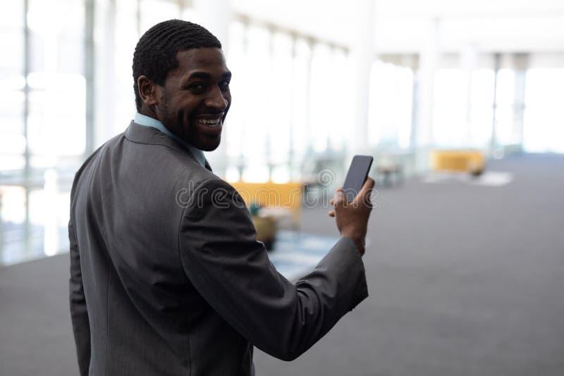 Επιχειρηματίας αφροαμερικάνων που χρησιμοποιεί το κινητό τηλέφωνο στην αρχή στοκ φωτογραφίες