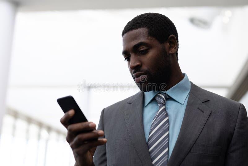 Επιχειρηματίας αφροαμερικάνων που χρησιμοποιεί το κινητό τηλέφωνο στην αρχή στοκ φωτογραφία με δικαίωμα ελεύθερης χρήσης