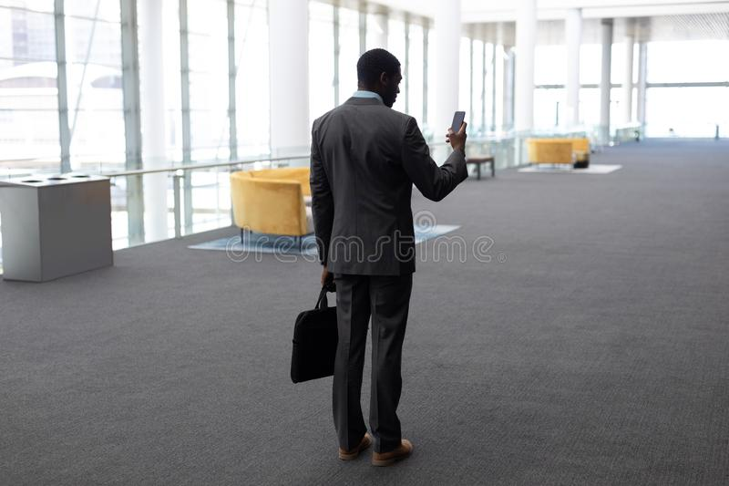 Επιχειρηματίας αφροαμερικάνων που χρησιμοποιεί το κινητό τηλέφωνο στην αρχή στοκ εικόνες με δικαίωμα ελεύθερης χρήσης