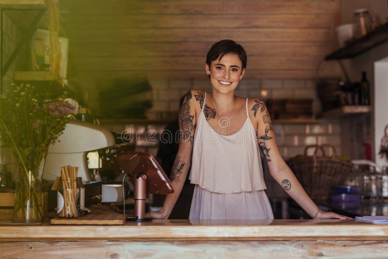 Επιχειρηματίας γυναικών που στέκεται στο μετρητή του καφέ της στοκ φωτογραφία με δικαίωμα ελεύθερης χρήσης