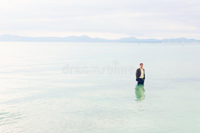 Επιχειρηματίας γόνατο-βαθιά στο νερό στοκ εικόνα