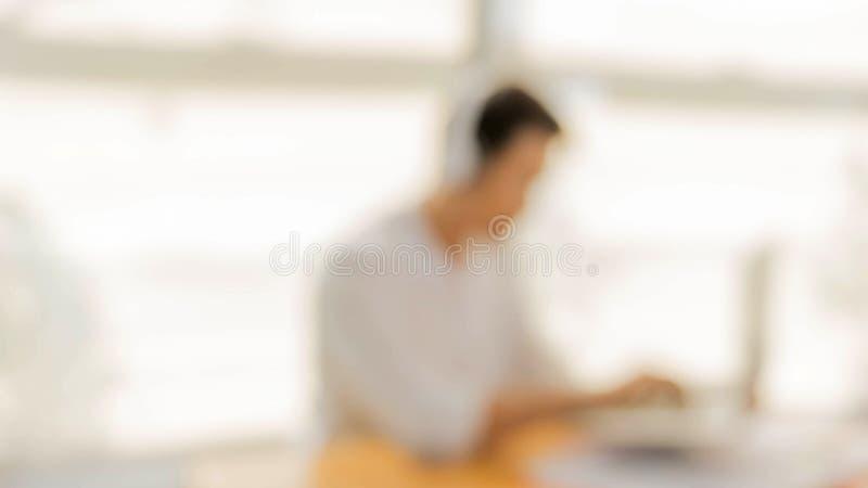Επιχειρηματίας θαμπάδων που φορά τα ακουστικά που τραγουδούν το τραγούδι και που χρησιμοποιούν το lap-top dur στοκ εικόνα