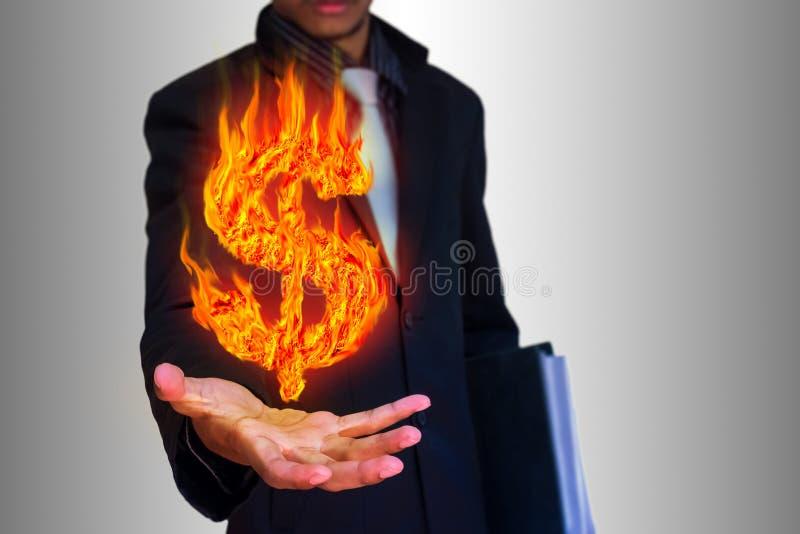 Επιχειρηματίας και αφηρημένο σύμβολο δολαρίων πυρκαγιάς στοκ εικόνα