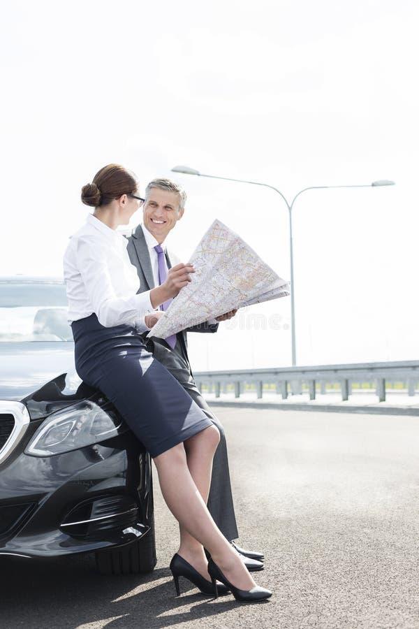 Επιχειρηματίας και γυναίκα που αναλύουν το χάρτη στεμένος έξω από το αυτοκίνητο στο δρόμο ενάντια στον ουρανό στοκ εικόνες με δικαίωμα ελεύθερης χρήσης