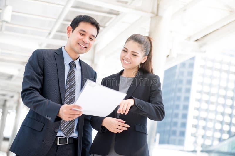 Επιχειρηματίας και επιχειρηματίας που συζητούν το έγγραφο στοκ φωτογραφία