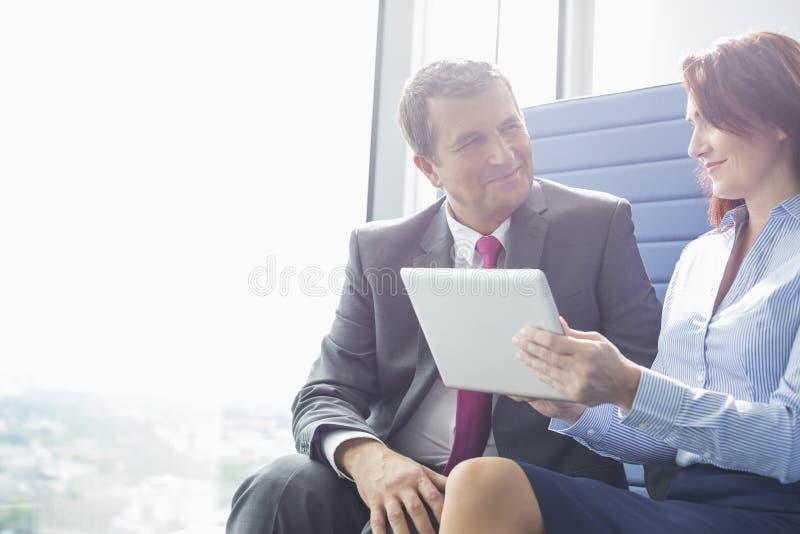 Επιχειρηματίας και επιχειρηματίας που χρησιμοποιούν το PC ταμπλετών στην αρχή στοκ εικόνες με δικαίωμα ελεύθερης χρήσης