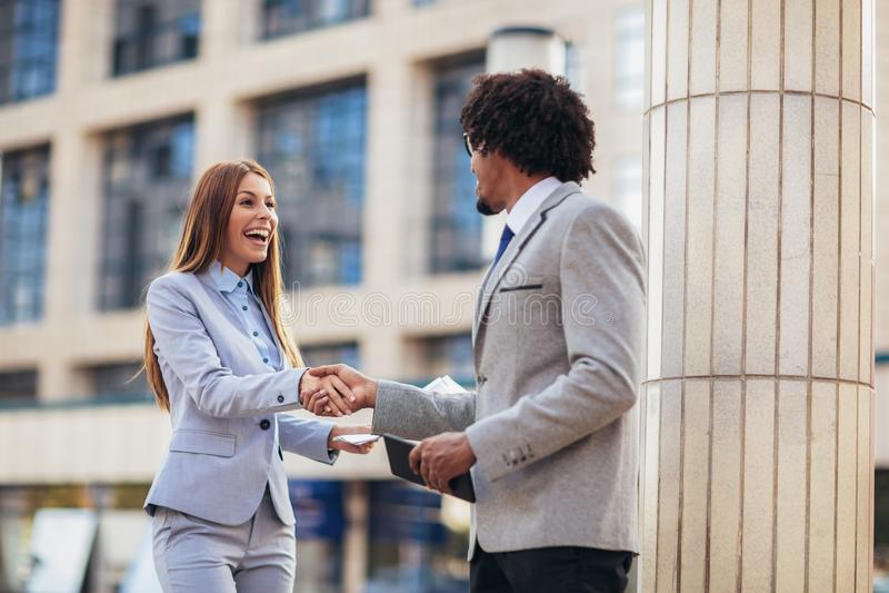 Επιχειρηματίας και επιχειρηματίες που τινάζουν τα χέρια έξω από το γραφείο στοκ φωτογραφίες