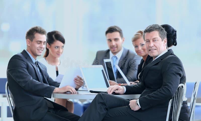 Επιχειρηματίας και η επιχειρησιακή ομάδα του με τα οικονομικά έγγραφα που κάθονται σε ένα γραφείο στο λόμπι της τράπεζας στοκ εικόνα