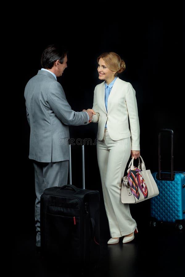 Επιχειρηματίας και μέσος ηλικίας επιχειρηματίας με τις βαλίτσες που τινάζουν τα χέρια στοκ φωτογραφία