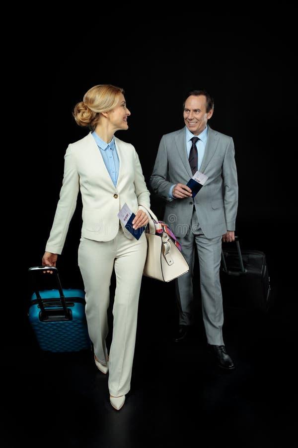 Επιχειρηματίας και μέσος ηλικίας επιχειρηματίας με τις βαλίτσες έτοιμες να σκοντάψουν στοκ εικόνα