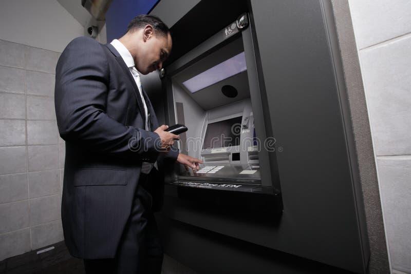 Επιχειρηματίας και μια μηχανή του ATM στοκ εικόνα