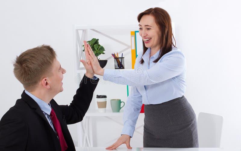 Επιχειρηματίας και επιχειρηματίας που δίνουν υψηλός-πέντε για την καλή εργασία στο υπόβαθρο γραφείων Επιχειρησιακή έννοια εμβλημά στοκ φωτογραφία με δικαίωμα ελεύθερης χρήσης