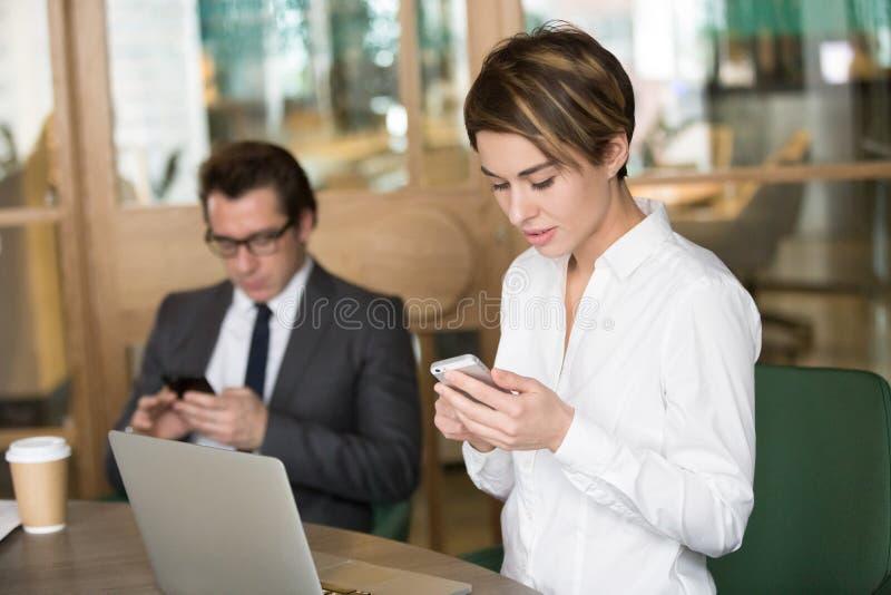 Επιχειρηματίας και επιχειρηματίας που χρησιμοποιούν τα κινητά τηλέφωνα για την εργασία μέσα στοκ φωτογραφία με δικαίωμα ελεύθερης χρήσης
