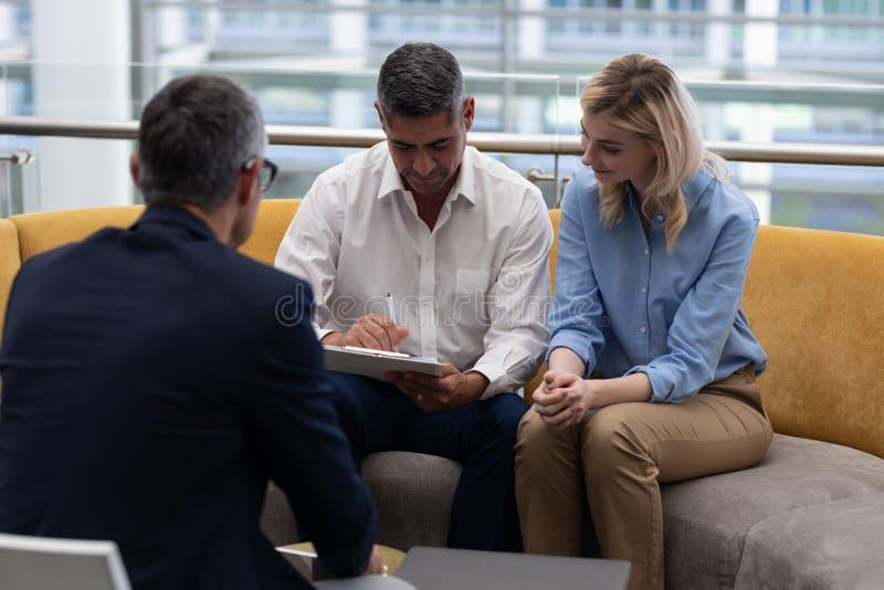 Επιχειρηματίας Καυκασίων που υπογράφει τα έγγραφα καθμένος στον καναπέ στοκ εικόνες