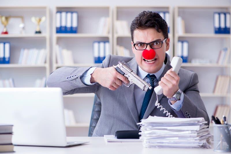 Επιχειρηματίας κλόουν που εργάζεται στο γραφείο που ματαιώνει με το α στοκ φωτογραφία