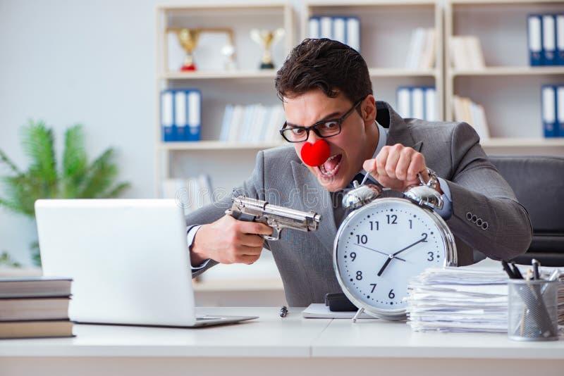 Επιχειρηματίας κλόουν που εργάζεται στο γραφείο που ματαιώνει με το α στοκ εικόνα με δικαίωμα ελεύθερης χρήσης