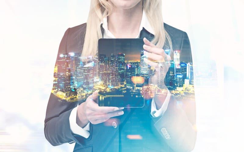 Επιχειρηματίας με έναν υπολογιστή ταμπλετών, πόλη νύχτας στοκ εικόνες