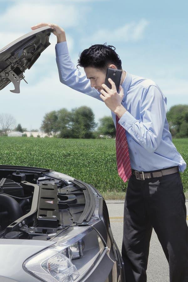 Επιχειρηματίας με ένα σπασμένο αυτοκίνητο στο δρόμο στοκ φωτογραφία με δικαίωμα ελεύθερης χρήσης