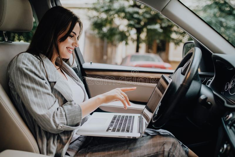 Επιχειρηματίας με ένα lap-top στο αυτοκίνητό της στην οδό στοκ φωτογραφίες