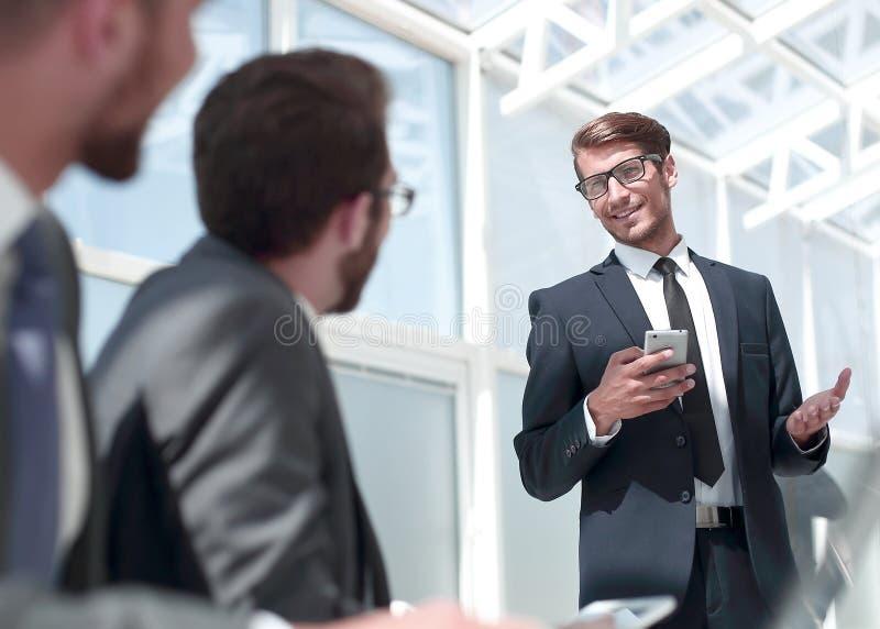 Επιχειρηματίας με ένα smartphone που στέκεται στο ofiice του στοκ φωτογραφία