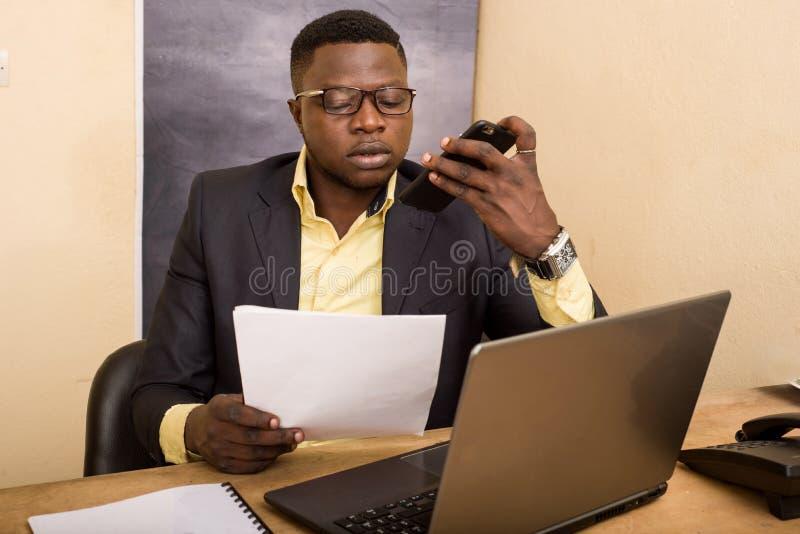 Επιχειρηματίας με κοστούμι στο γραφείο μιλάει στο κινητό τηλέφωνο στοκ εικόνα