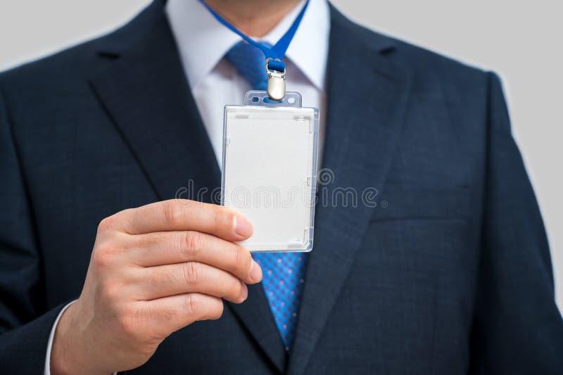 Επιχειρηματίας με κοστούμι, φορώντας λευκή ταυτότητα ή κάρτα ονόματος σε φύλλο σε έκθεση ή συνέδριο στοκ εικόνες