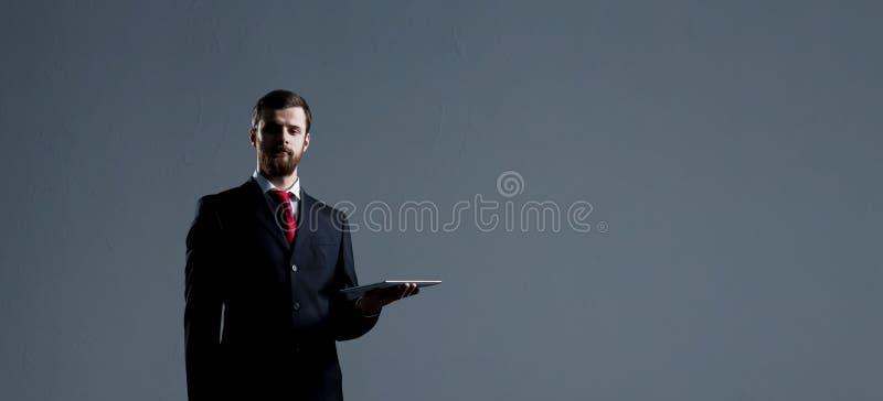 Επιχειρηματίας με μια συσκευή ταμπλετών Μαύρο υπόβαθρο με το copyspac στοκ φωτογραφίες