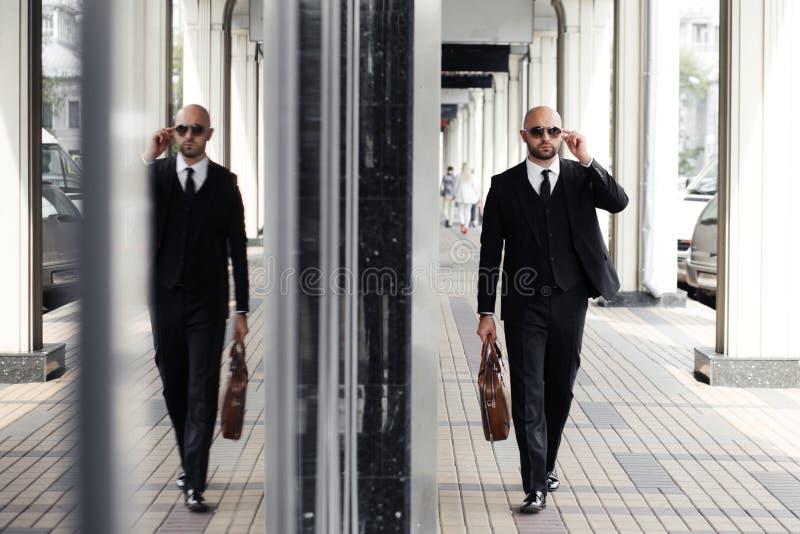Επιχειρηματίας με μια τσάντα κοντά στο γραφείο που μιλά στο τηλέφωνο στοκ φωτογραφία με δικαίωμα ελεύθερης χρήσης