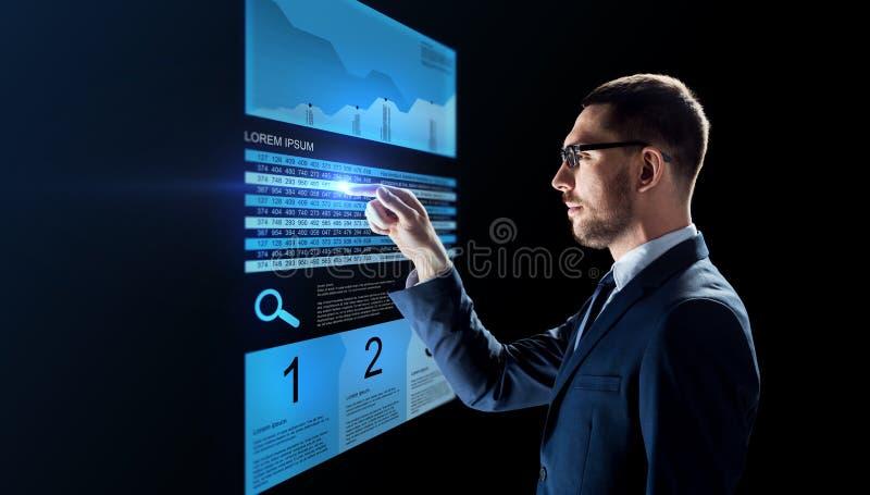 Επιχειρηματίας με τα διαγράμματα αποθεμάτων στις εικονικές οθόνες στοκ εικόνες
