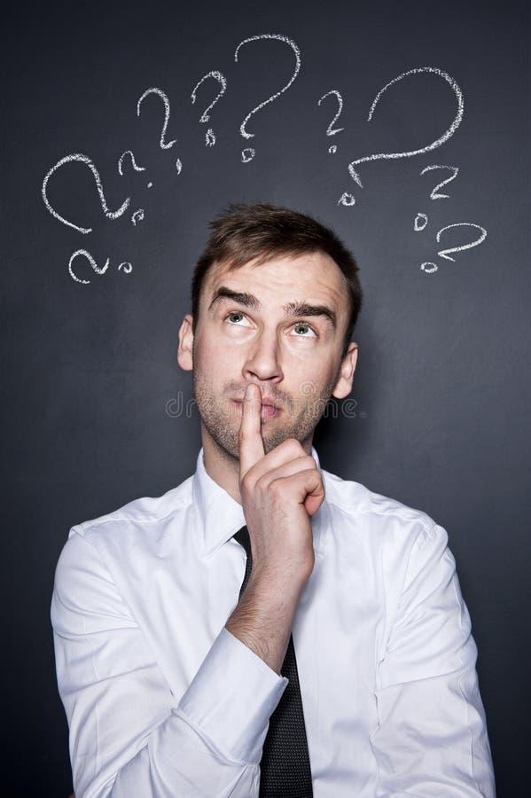 Επιχειρηματίας με τα ερωτηματικά στοκ εικόνες