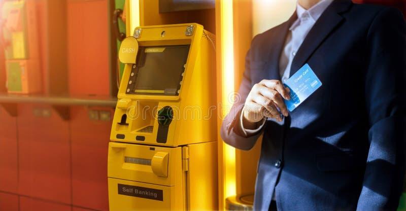 Επιχειρηματίας με την πιστωτική κάρτα υπό εξέταση, ATM για τη ανάληψη μετρητών στοκ εικόνες